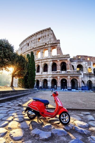 Italy, Rome, a red Vespa motorbike in front of Colosseum at sunrise