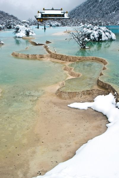 The Five-Color Ponds are situated at the back of the rear temple, Huang Long Temple, Huanglong National Park, Sichuan Province, China. Due to varied depth of the ponds and all kinds of mineral pigments and deposits on the bottom