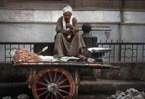 photography philip dunn/cairo street seller sits barrow smoking cigarette